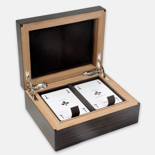 Coffret à jeux - 17 x 13 x 7 cm . Deux jeux de cartes bridge Ebène de Macassar avec incrustation de nacre abalone Les baguettes d'angle en ébène du Gabon soulignent la profondeur de l'ébène de Macassar. L'intérieur est entièrement gainé de velours marron, avec molleton sur le gainages du couvercle. Les deux casiers qui reçoivent les jeux de cartes sont équipés avec une languette en Alcantara qui facilite l'extraction des jeux. Signature à l'intérieur du coffret par l'Incrustation trois points de nacre. Estampille au fer chaud sur le fond.